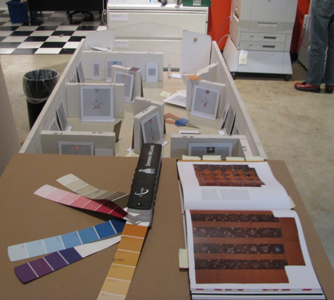 Color swatches, catalog open to a featured quilt, and the gallery model.