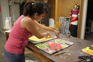 Araceli puts finishing touches on her panel for the mural.