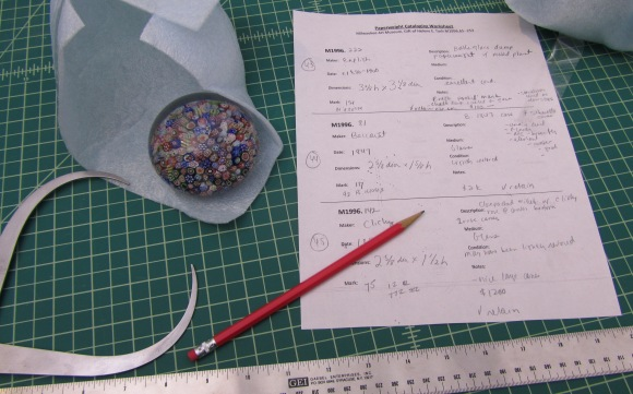 Cataloging paperweights. Photo by the author.