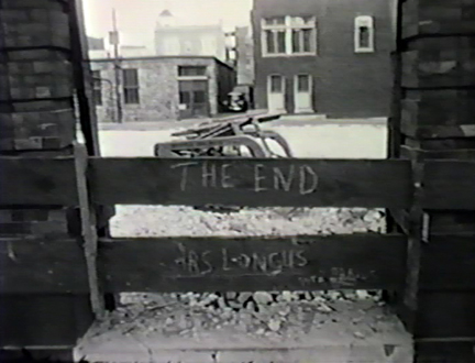 "Film still: Demolished portion of the Layton Art Gallery, displaying the scrawled phrase ""The End – Ars Longus"", circa 1957. Milwaukee Art Museum, Institutional Archives."