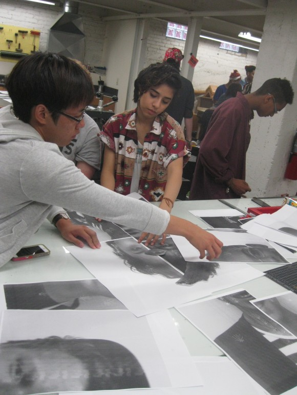 Teens work with portrait photos to begin the artmaking process. Photo by Tim Abel