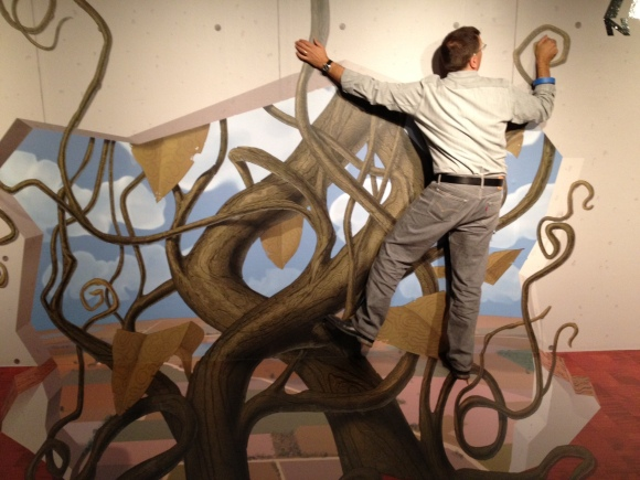 "Exhibition Designer David Russick ""climbs"" a vine. Photo by Brigid Globensky"