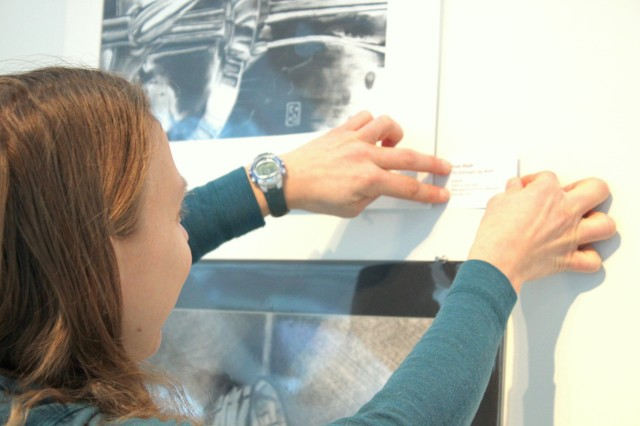 Art Preparator Kelli Busch affixes one of the labels to the gallery wall. Photo by Chelsea Emelie Kelly