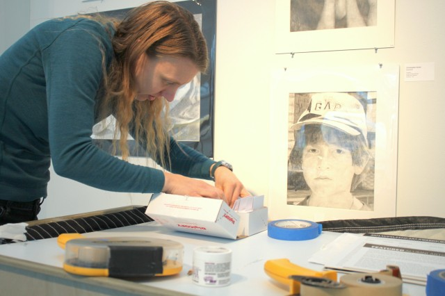 Art Preparator Kelli Busch prepares labels for the gallery walls. Photo by Chelsea Emelie Kelly