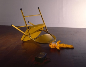 Tony Oursler (American, b. 1957), MMPI (Self-Portrait in Yellow), 1996. Video installation with video projector, VCR, video tape, small cloth figure, and metal folding chair. Dimensions variable. Milwaukee Art Museum, Purchase, with funds from Donald and Donna Baumgartner, Marianne and Sheldon B. Lubar, Allen and Vicki Samson, Dr. and Mrs. Philip Shovers, and Sibyl and David Wescoe. M1998.136a-i. Photo credit: Larry Sanders