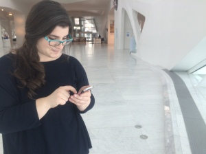 Michelle Bastyr, Kohl's Art Generation Community Relations Coordinator, uses her iPhone in the Museum's Windhover Hall. Photo by the author