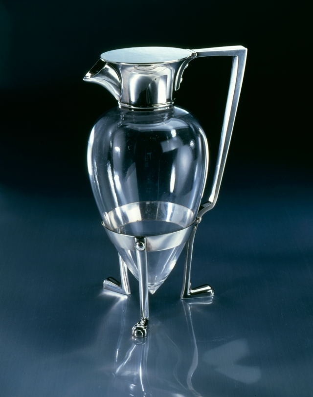 "Christopher Dresser (English, 1834-1904), Manufactured by Hukin & Heath (Birmingham, England, established 1885), ""Crow's Foot"" Claret Jug, designed October 3, 1878. Silver plate and glass, 9 5/16 × 6 1/2 × 4 1/4 in. (23.65 × 16.51 × 10.8 cm). Milwaukee Art Museum, Purchase, by exchange M1998.75 Photo credit: Historical Design."